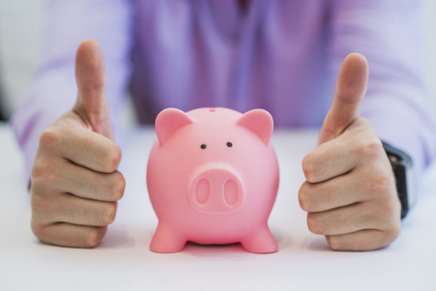 Successful business man with piggy bank holding thumbs up in off