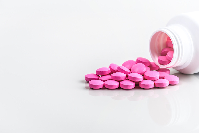 Pink pills are scattered from a jar on a white background.